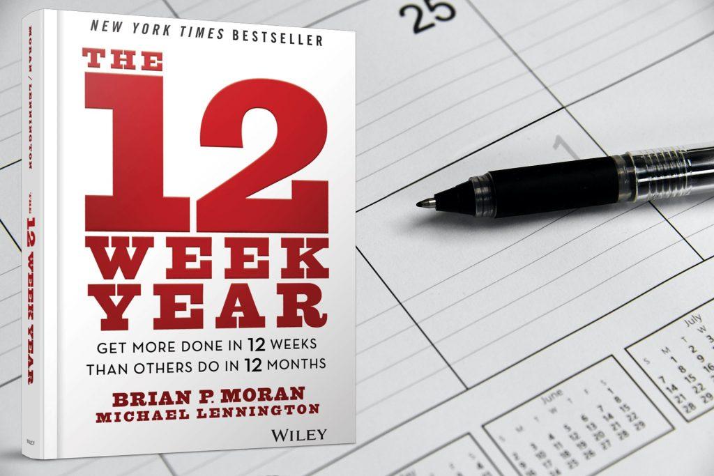 Boek The 12 Week Year met een kalender en een pen op de achtergrond