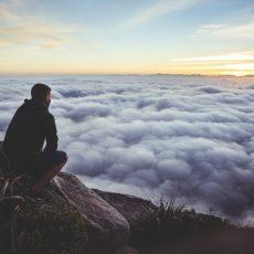 Gehurkte man hoog op een berg die over een wolkendek heenkijkt