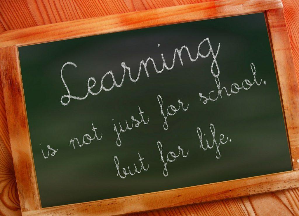 Klein krijtbord met daarop de tekst 'Learning is not just for school, but for life'.