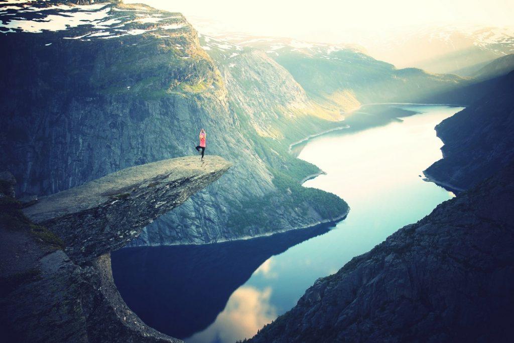 Vrouw die in yoga-positie staat en uitkijkt over een meer tussen de bergen