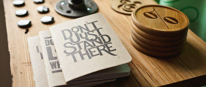 Schriften op een houten tafel met op het bovenste schrift de tekst 'Don't just stand there'