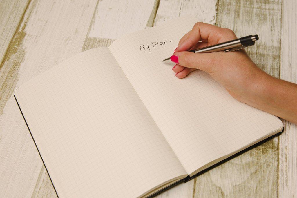 Een pen in een hand die geplaatst is onder de enige tekst die op de twee verder lege pagina's staat: My Plan.