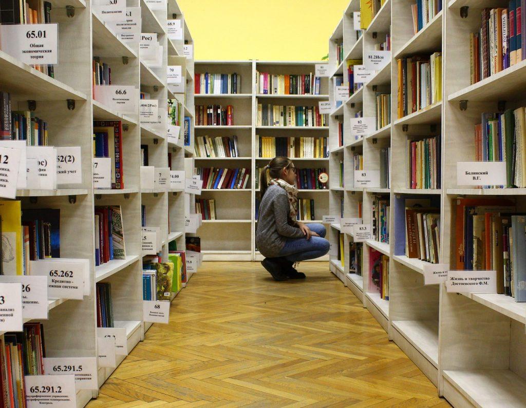 Studente die op haar hurken zit voor een kast met boeken in een bibliotheek