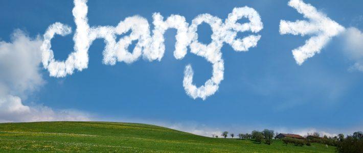 Het woord 'Change' met een pijl erachter geschreven met wolkjes in de lucht