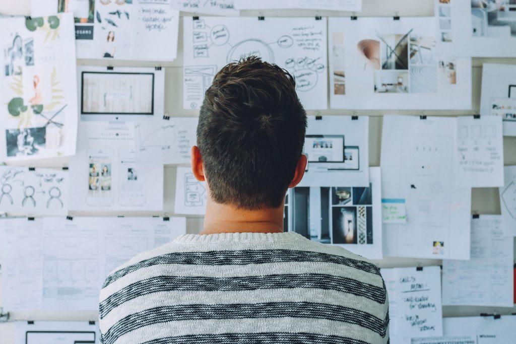 Man kijkt naar een wand vol schetsen en andere papieren