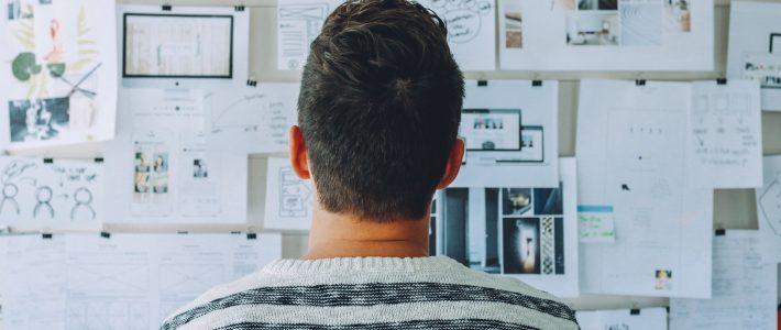 Achterkant van het hoofd van een man die naar een prikbord met allerlei papieren kijkt
