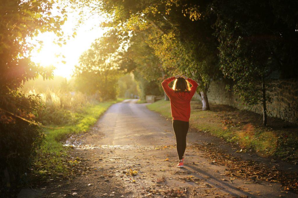 Vrouw wandelt 's ochtends over een pad in de natuur