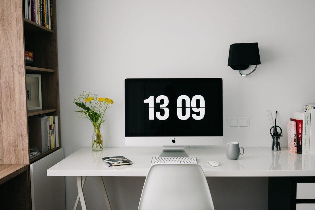 Bureau met daarop een beeldscherm met daarop de tijd: 13:09.