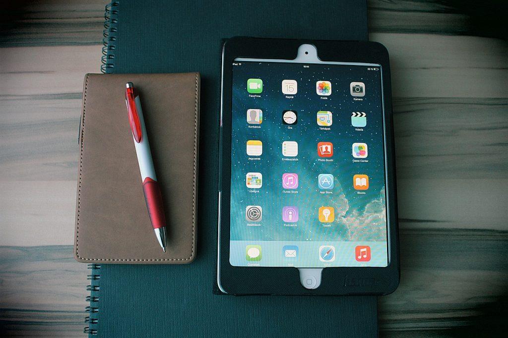 Notiteblok en pen, iPad en smartphone