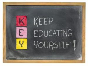 De letters KEY onder elkaar op sticky notes geplakt op een krijtbord met daarnaast gekrijt: Keep Educating Yourself