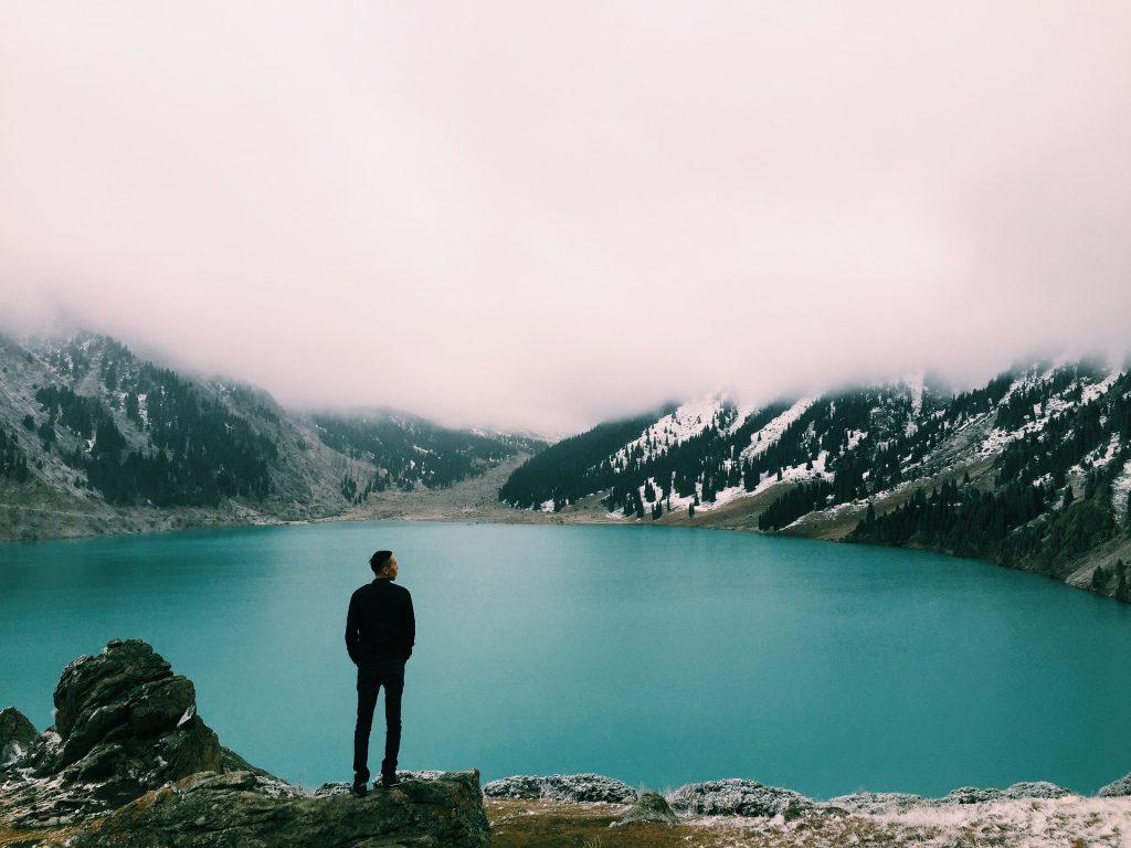 Man staat te kijken naar een meer tussen de bergen