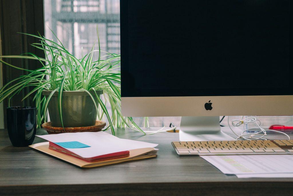 iMac op een bureau met daarachter een plant in de vensterbank