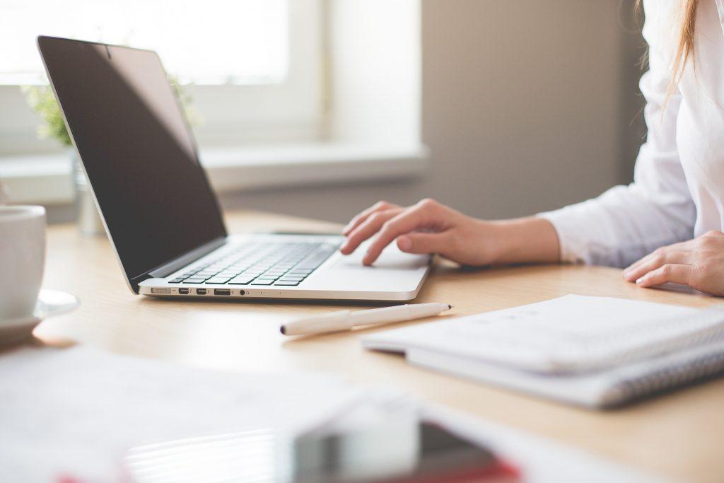 Vrouw achter laptop en notitieboek