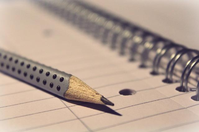Sterk ingezoomd op een notitieblok en een potlood.