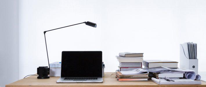 Bureau met laptop en stapels boeken, papieren en mappen