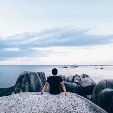 Man zit op rotsen en kijkt uit over zee