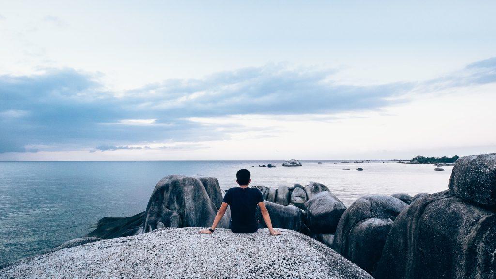 Man die op een rots zit en over de zee uitkijkt