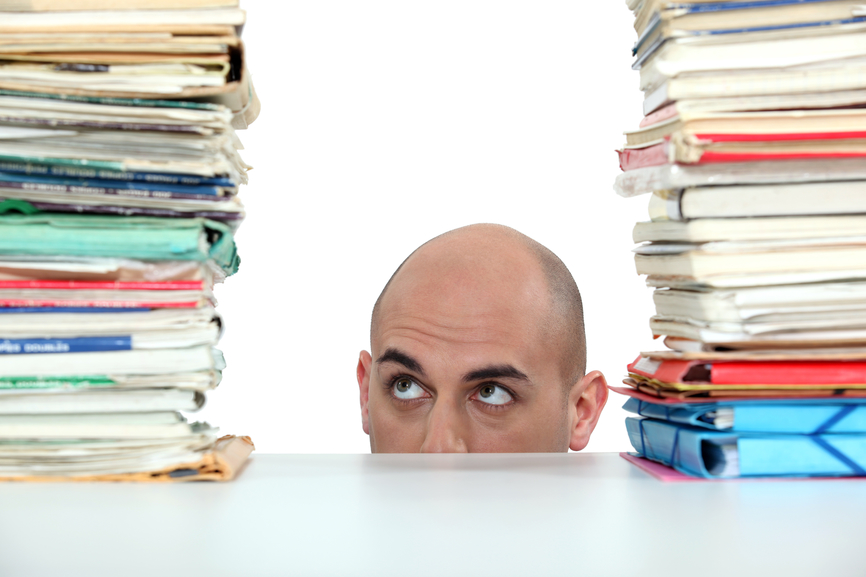 Head of businessman between two large stacks of paperwork